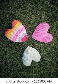 three colorful hearts shape made from yarn, pink, rainbow and light blue lay on grass field, arrage in good position. image of soft object for Valentine's day convey feeling of love and care