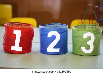 three colorful jars with drawn numbers 1 2 3 on the school table