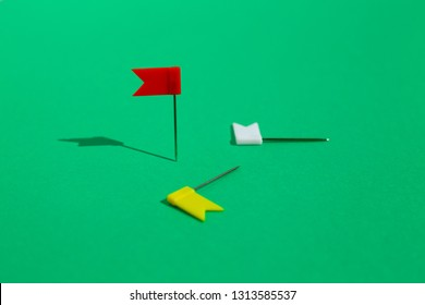 Three colorful little flag pins pinned on a green surface. Business or travel concept. The Goals