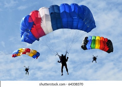 Three colorful parachutes on blue sky.