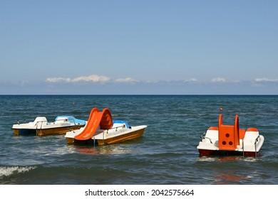 Three colorful pedalboats anchored in the sea shore of the Maremma coast in Tuscany, Italy