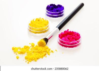 Three colorful powder eyeshadows with a makeup brush