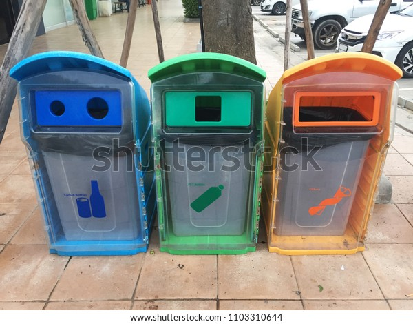 Three colorful recycle bins in public.
