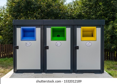 Three colorful recycle bins in urban environment. Garbage can for separately sorting biodegradable trash in different bins. Waste management recycling point in a small city in Romania