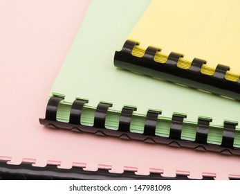 Three colorful ring notebooks staple