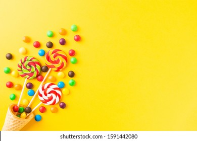 Three colorful round candies on sticks in waffle cone over yellow background with copy space. Top view. Flat lay