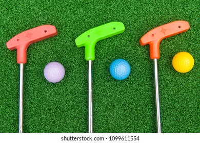 Three colorful rubber golf clubs with balls for miniature golf