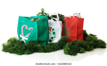 Three colorful shopping bags filled with Christmas goodies.  On a white background.