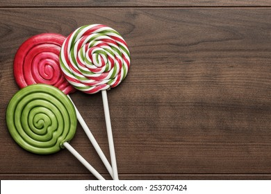 three colorful sugar lollipops on the wooden table