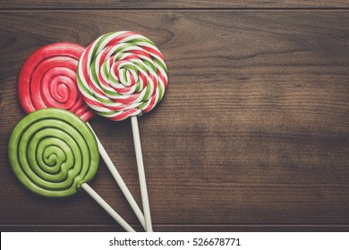 three colorful sugar lollipops on wooden table