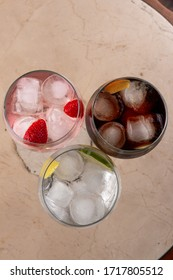 Three colorful tonica cocktails with fruits on marble background. Set of tonica cocktails with fruits served in glass cups on light background. Overhead shot