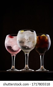 Three colorful tonica cocktails with fruits on dark background. Set of tonica cocktails with fruits served in glass cups on dark background. General shot