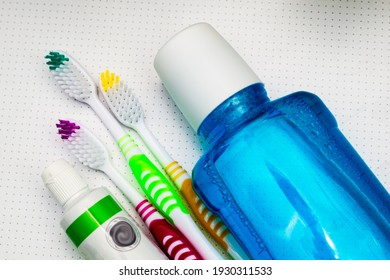 three colorful toothbrushes a tube of toothpaste and a mouthwash lie on the bathroom table close up
