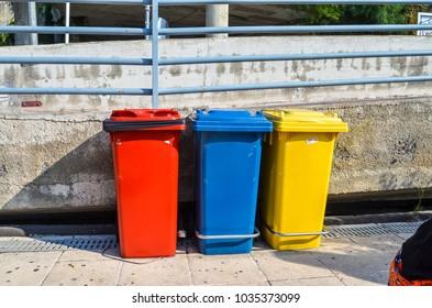 Three colorful trash bins for garbage separation