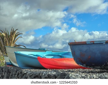 """three colorful wooden fishing boats in close-up on the pebble beach of lava stones in """"Bombilla"""" on """"La Palma"""". A blue sky above with little white clouds"""
