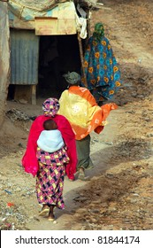 Three colorfully dressed women and a baby walking away from the camera in a town in West Africa
