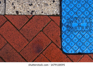 Three colors texture of sidewalk floor and water meter cover.