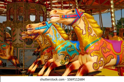 Three colourful horses on a fairground carousel ride