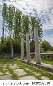 Three columns and trees and sky at Aizonai, Anatolia, Turkey.