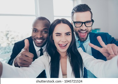 Three comic, funny, crazy partners, colleagues having fun, men with bristle showing like symbol and two fingers, peace sign with hands, girl shooting selfie and gesture tongue out, wink with one eye