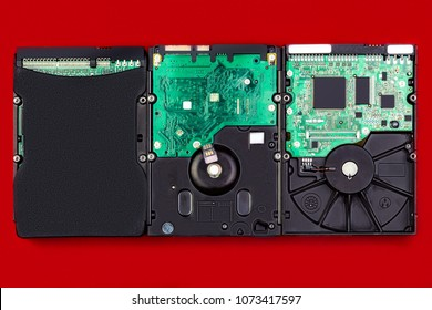 Three computer hard drives on a red background, top view. The concept of data storage technology