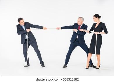 Three concentrated businesspeople pulling rope on isolated on white
