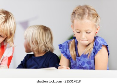 Three concentrated schoolgirls painting pictures