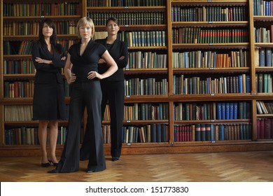 Three confident female lawyers standing in library