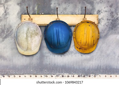 Three construction helmets hanging on an old wooden hat-rack
