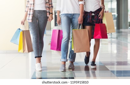 Three consumers with paperbags walking down shopping center