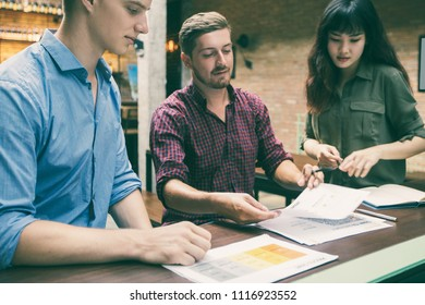 Three content young business people wearing casual clothes, working with documents, discussing ideas, standing and sitting at cafe counter