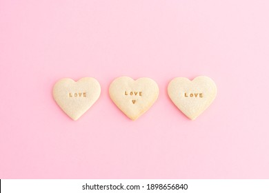 Three Cookies in the shape of a heart and the word LOVE on a pink background. Valentine's Day, Mother's Day, anniversary. Copy space. Top view.