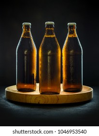Three cool beer bottles on wooden tray and black background