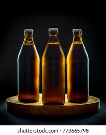 Three cool beer bottles on wooden tray