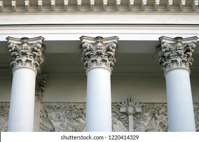 Three corinthian columns supporting the cornice of the church, white bulding in greek style