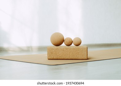 Three cork massage balls for fascia on a cork block on a cork yoga mat. Concept: eco friendly and biodegradable props for self care at home