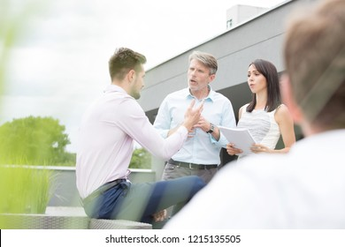 Three corporate business people having an argument outside whilst discussing work. Either he is mentoring the or it looks like their are having a professional fight.