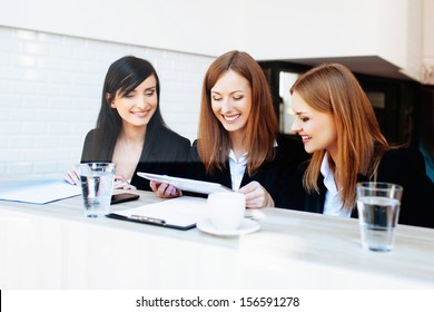 Three corporate businesswoman meeting in cafe.