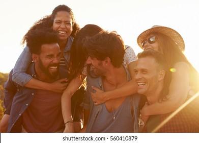 Three couples having fun piggybacking at sundown