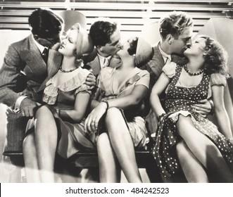 Three couples kissing