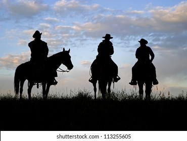 Three cowboys silhouetted against a dawn sky. Montana horse ranch