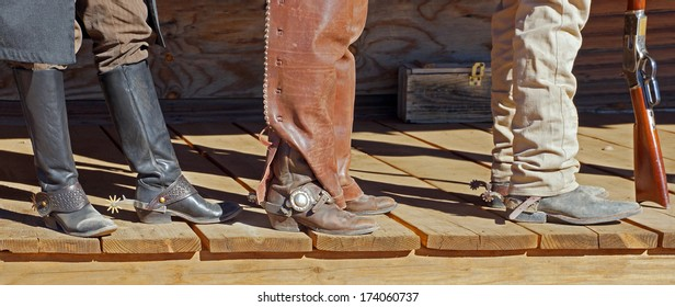 Three cowboys stand on the porch showing their dusty boots and spurs