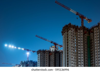 Three cranes and building at night