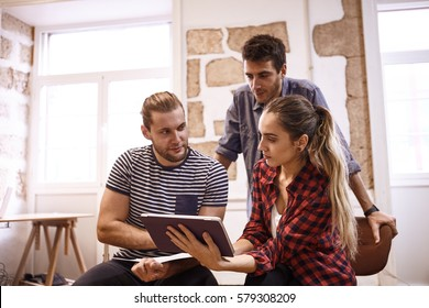 Three creative young business people sharing ideas with each other, looking at a tablet while in a brightly lit office