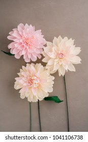 Three crepe paper dahlias on brown wooden background