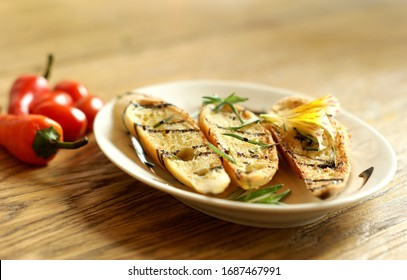 Three crispy grilled bread toasts with basilico sauce and green rosemary and yellow flower decoration on white plate with red chilli pepper in background on the bright wooden table