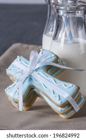 Three (cross shaped) Cookies on tan napkin with milk bottles