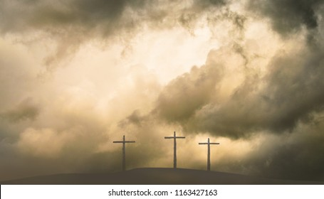 Three Crosses on Hill in Storm with Gold Sky