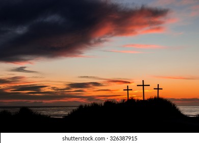 Three Crosses on a sand dune with the sun setting behind them.