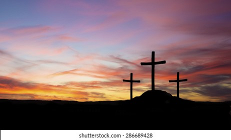 three crosses in silhouette on a hill with sunset